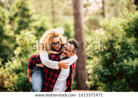 Happy adult caucasian couple in relationship and love play together in the forest wood nature - outdoor people leisure activity concept with cheerful caucasians