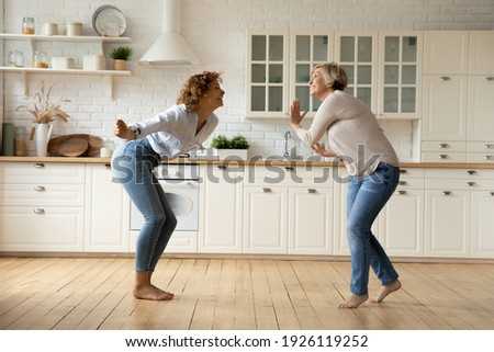 Happy adult daughter and senior mother dancing at modern kitchen after changing interior design moving to new house. Excited mature mom and grown female child celebrate renovation buying new furniture