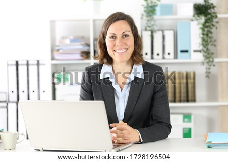 Happy adult executive woman posing looking at camera sitting on a desk at the office