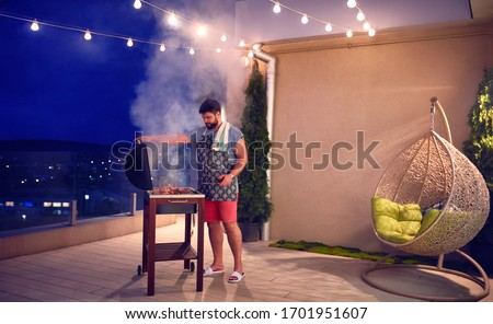 happy adult man grilling the barbecue on rooftop terrace at home in the evening