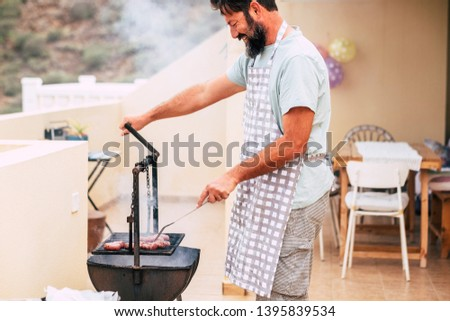 Happy adult man with beard cooking meat with grill barbecue at home for friends to have fun together - real life scene of people house lifestyle with bbq and food
