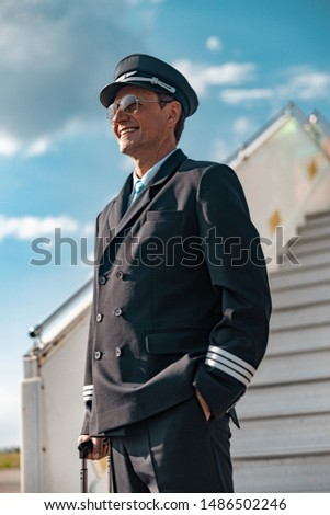 Happy adult pilot in uniform standing near plane ladder stock photo. Airway concept #1486502246