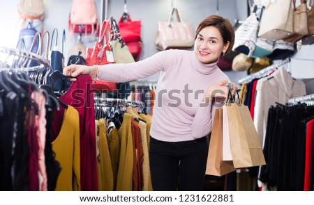 Happy adult woman choosing colorful blouse in women's cloths shop
