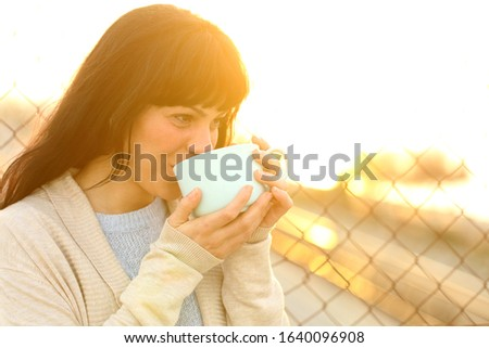 Happy adult woman drinking coffee at sunset in the street