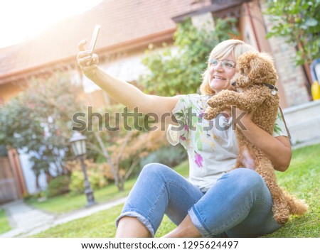 Happy adult woman taking a picture with domestic dog poodle in back yard
