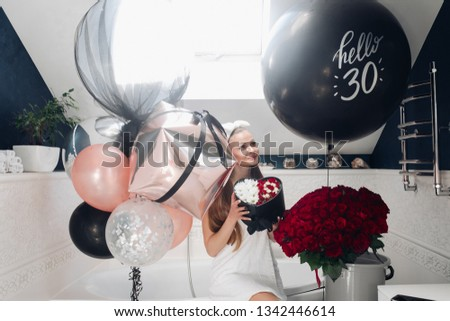 Happy adult woman with flowers and air balloons in bathroom.