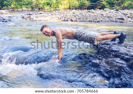 Happy adventurer sporty man  is washing himself on the bank of a mountain river. Wonderful sunny day for travel. #705784666