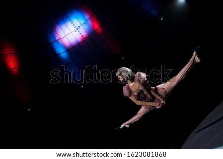 happy aerial acrobat in costume doing splits on rope