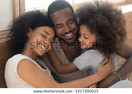Happy affectionate african american family of three bonding embracing, cute kid child daughter and loving parents cuddling congratulating dad with fathers day hugging smiling daddy laughing together