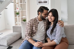 Happy affectionate indian couple bonding, hugging and laughing sitting on couch at home. Smiling young husband and wife embracing, having fun together, enjoying talking relaxing on sofa in apartment.