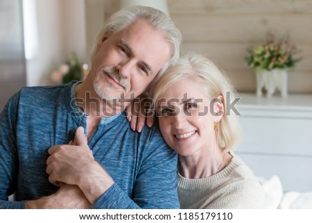Happy affectionate mature old man and woman embracing looking at camera, middle aged retired romantic family couple cuddling posing, love care devotion in senior people marriage, headshot portrait