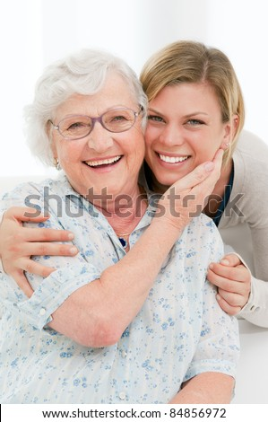 Happy affectionate senior woman embrace her granddaughter at home