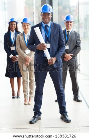 happy african american architect standing in front of colleagues in modern office