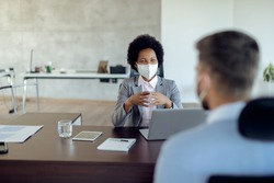 Happy African American bank manager talking to her client and wearing a face mask in the office due to coronavirus epidemic.