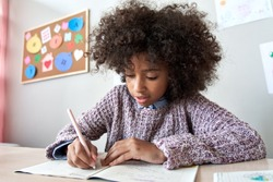 Happy african american black preteen school girl studying in classroom sitting at desk. Smart cute mixed race kid primary school student writing in exercise book doing homework, learning at home.