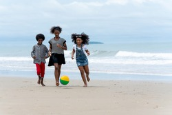 Happy African American boys and girls playing beach football together along the tropical beach on vacation in the summertime. Group of a family having fun at the seashore in the summer travel holiday