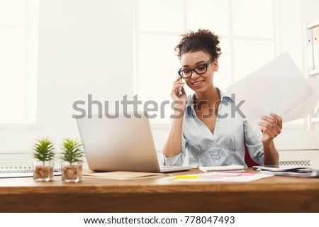 Happy african-american business woman talking on mobile at office. Young female manager consulting on phone, holding papers, using laptop at working place, copy space stock photo
