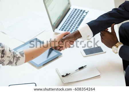 Happy african American businessman handshaking with client or competitor closing deal in an office interior with a wooden background. interview concept, close up #608354264