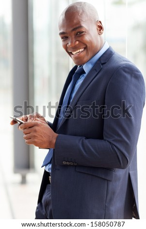 happy african american businessman reading email on smart phone