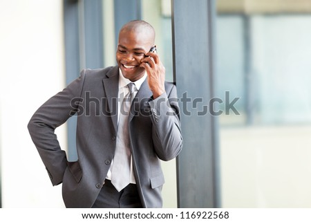 happy african american businessman talking on mobile phone in modern office