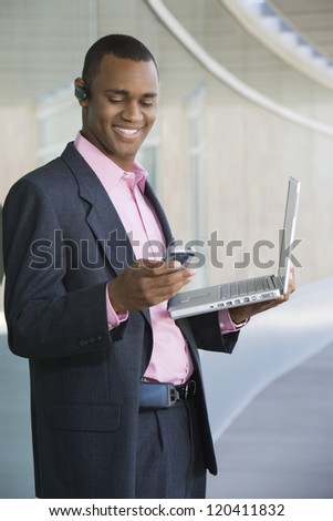 Happy African American businessman using mobile phone while holding laptop
