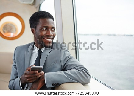 Happy African-american businessman with smartphone sitting by steamer window and looking through it