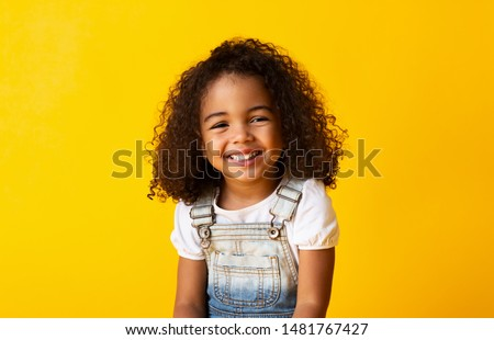 Happy african-american child girl smiling to camera over yellow background stock photo