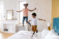 Happy african american children jumping at bedroom. Smiling and laugh diverse siblings enjoying weekend together at living room. Successful mortgage, cute kids on bed at new warm house.