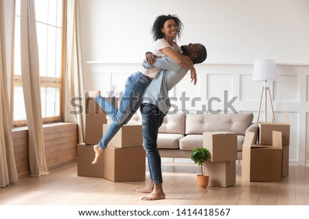 Happy african american couple first time home buyers celebrate new house purchase on moving day, smiling husband embracing lifting excited young wife laughing standing among boxes in own flat house