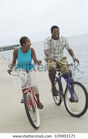 Happy African American couple riding bicycle at beach