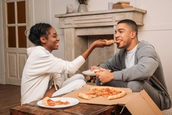 happy african american couple sitting on floor, woman feeding man pizza at home