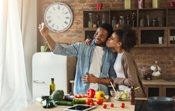 Happy african-american couple taking selfie with smartphone while preparing salad at kitchen