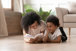 Happy african american cute little boy listening single mommy or female babysitter, reading funny story or fairy tales. young black woman having fun, spending leisure time, lying on floor with son.