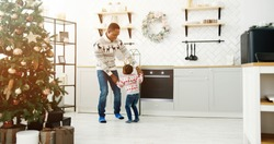 Happy African American dad and little kid listen music and dancing in modern cozy house kitchen decorated with xmas tree twinkle lights on Christmas Eve. Happy family enjoy free time, holidays concept