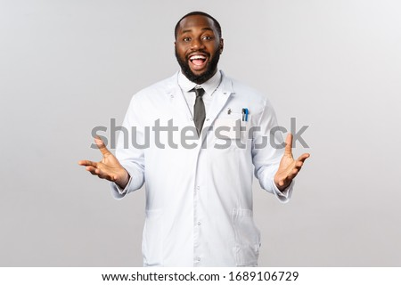 Happy african american doctor at clinic or hospital welcoming patient, telling good news to family after treating person from covid19 severe sympthoms, gesturing and smiling, wear white coat