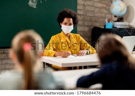 Happy African American elementary teacher wearing face mask while giving a lecture to her students in the classroom.