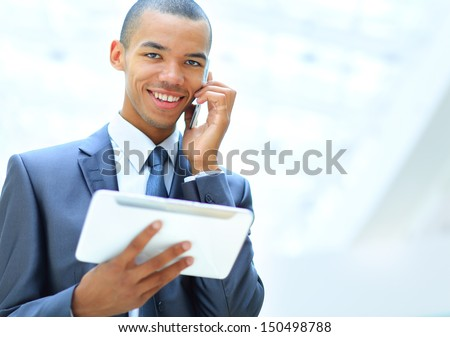 happy african american entrepreneur using tablet computer and talking on phone
