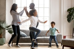 Happy african american family and funny active children having fun dancing together at new home, cheerful black parents and two kids enjoying moving to music spending weekend time in living room