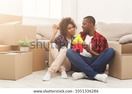 Happy african-american family couple with house and key symbols. Sitting on floor against near storage boxes at new apartment. Moving and real estate concept, copy space, isolated #1051336286