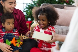 Happy African American family enjoying Christmas holiday. Cute African American little smiling girl receiving Christmas gift box or presents gift from adult hand. Merry Christmas and Happy Holidays