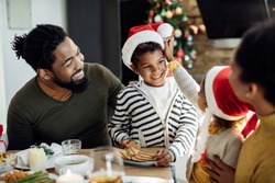 Happy African American family having fun at dining table while eating Christmas cookies. Focus is on boy.