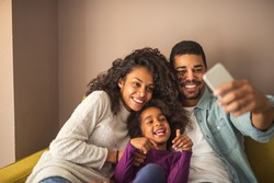 Happy african american family making  a selfie at home.