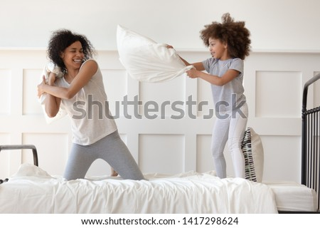 Happy african american family mixed race mom and little cute daughter having fun pillow fight on bed, smiling single mother laugh play funny game with small active child girl in bedroom on leisure