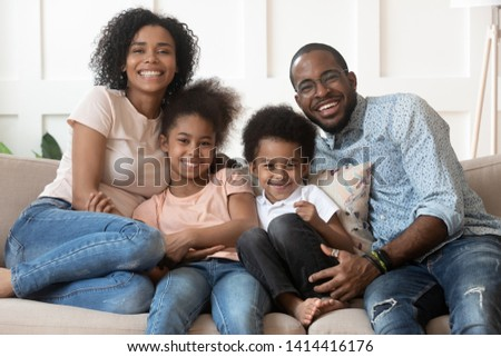 Happy african american family of four bonding looking at camera at home, smiling black parents and cute little kids sit on sofa, mixed race mom dad with small children embrace on couch, portrait