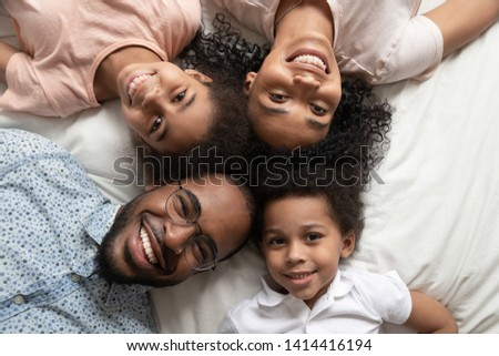 Happy african american family of four bonding lying on bed, black parents and cute little kids with smiling faces looking at camera in bedroom, mixed race mom dad with children portrait, top view