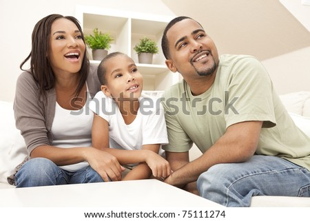 Happy African American family, parents and son, sitting on a sofa at home laughing and smiling