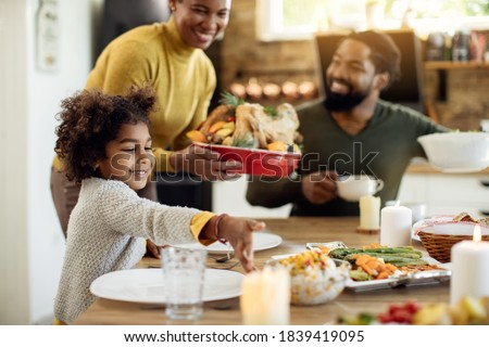 Happy African American family serving food for Thanksgiving lunch at dining table. Focus is on little girl.