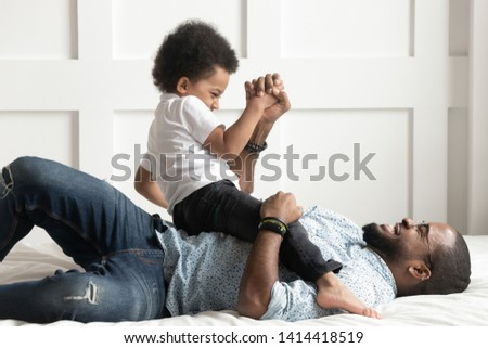 Happy african american family single dad laugh play with little son on bed, cute small kid boy having fun with black father tickle cuddle bonding in bedroom, child and daddy funny leisure moments