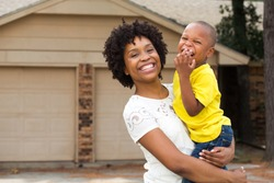 Happy African American Family. Single mom standing in front of her home with her little boy.