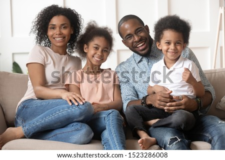 Happy african american family sitting on couch portrait. Smiling dad hold preschool son on knees, excited black mom embracing cute daughter, looking at camera, lazy weekend spending together at home. Stockfoto ©